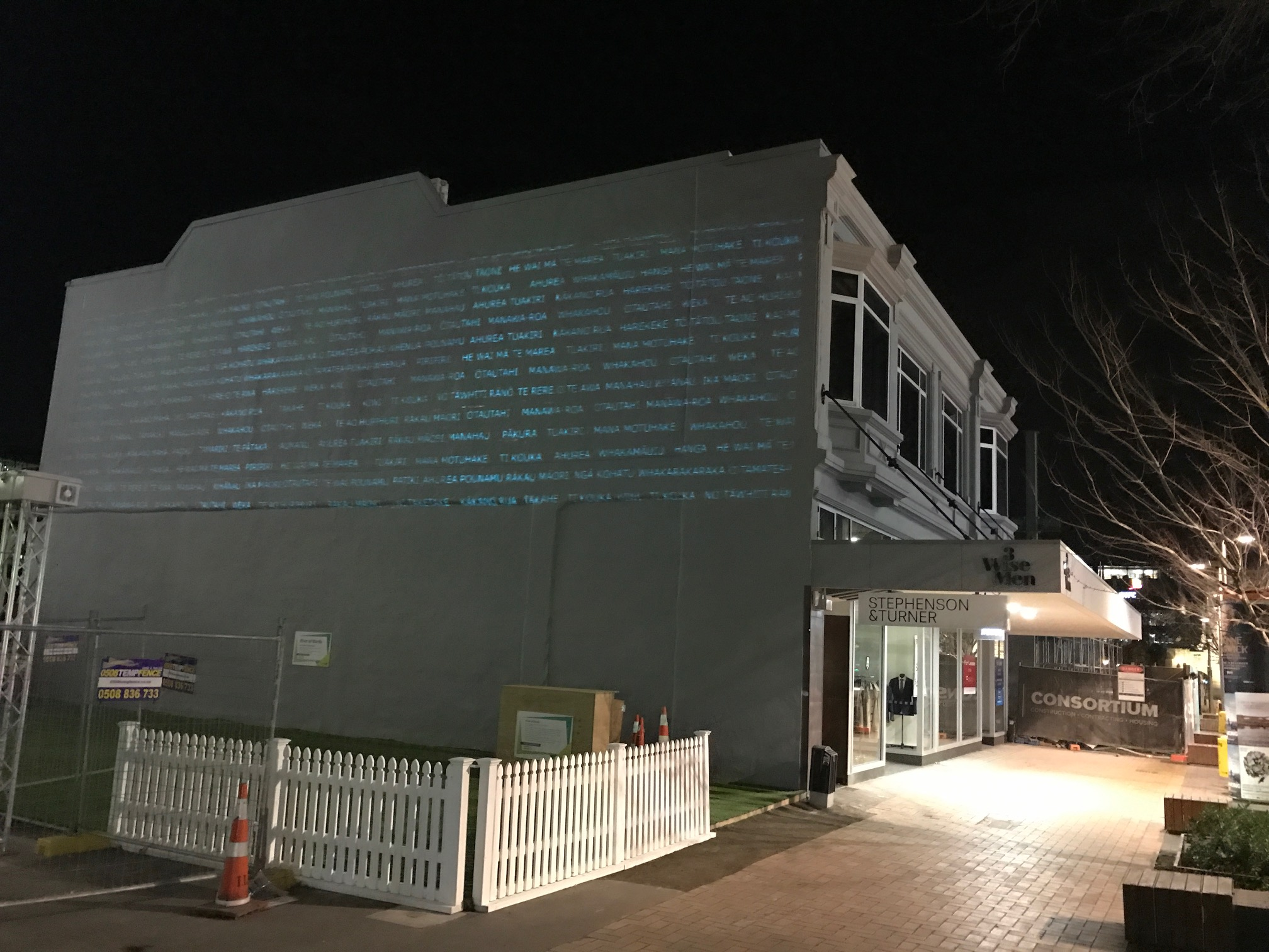A blank wall features a projected poem