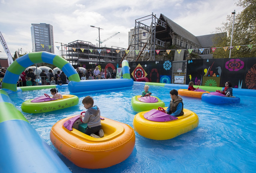 Children play bumper boats in front of the Cathedral
