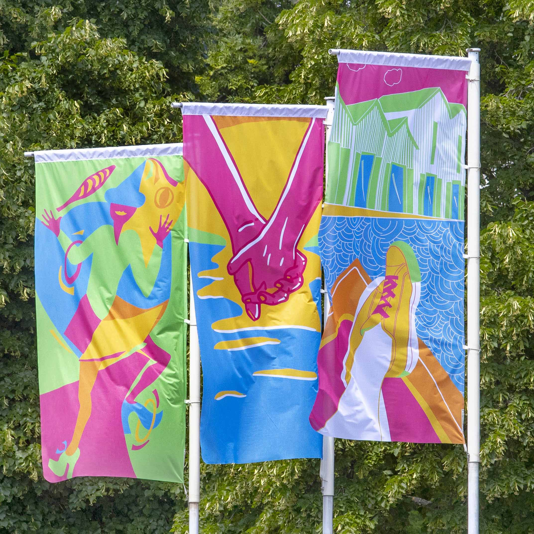 Three colourful street flags displayed beside a tree